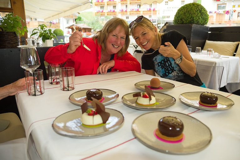 two women eating dessert and smiling in the dolomites italy
