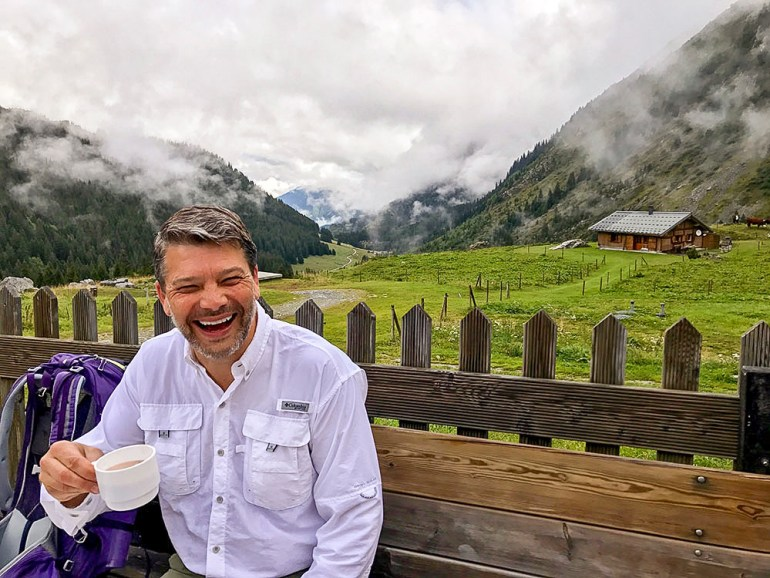 man smiling with a cup of coffee in his hand and the alps behind him