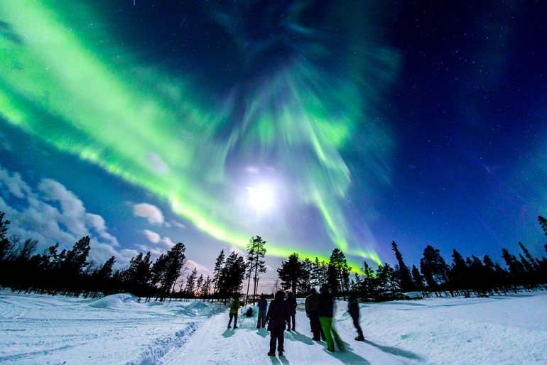 northern lights over hikers in finland