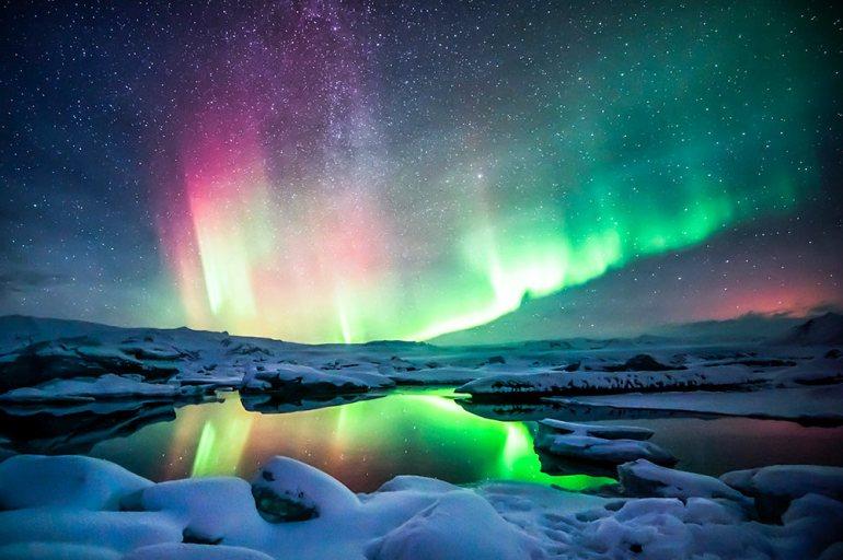 northern lights over snowy lagoon