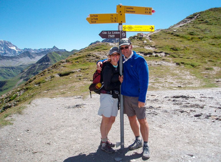 couple standing near signpost on the tour du mont blanc trail