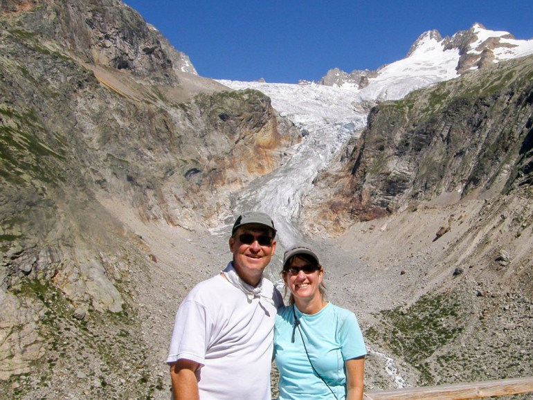 two hikers standing in front of a glacier on the tour du mont blanc