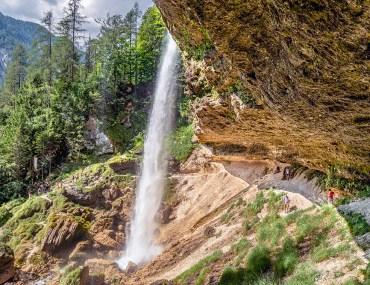walking beneath a waterfall in Slovenia