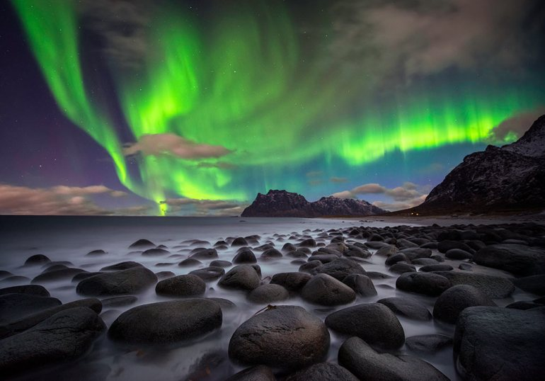 northern lights over beach in iceland