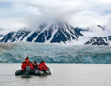 zodiac and people with red jackets approaching a glacier