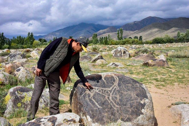 man near petroglyph in Kyrgyzstan