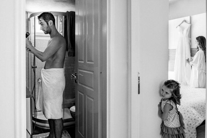 little girl watching parents get ready for wedding