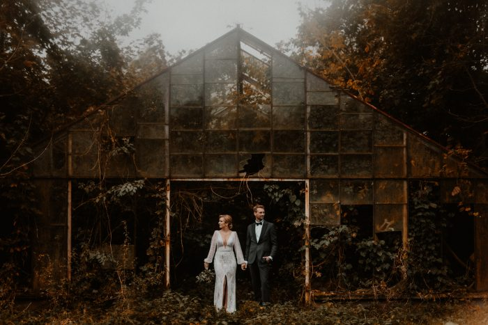 couple in front of overgrown greenhouse