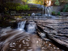 Double adirondack waterfall with foram swirl in water and golden light