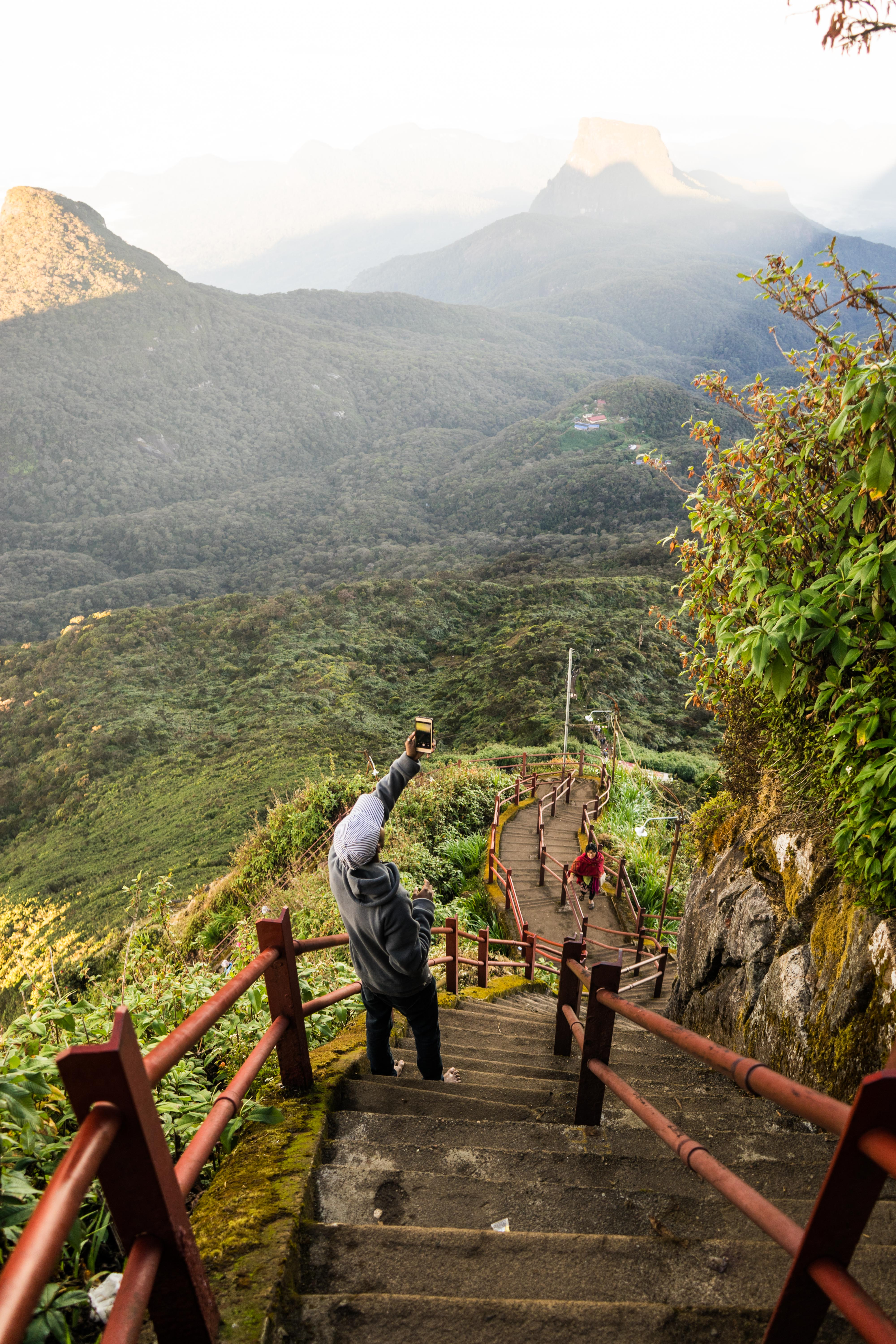 Stairs leading up to Adams peak in front of a jungle landscape.