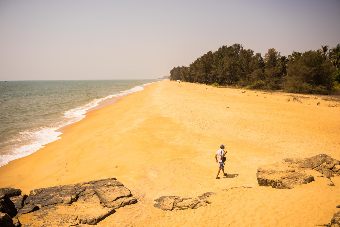 A single person walking along a nearly untouched beach in Kappil, India