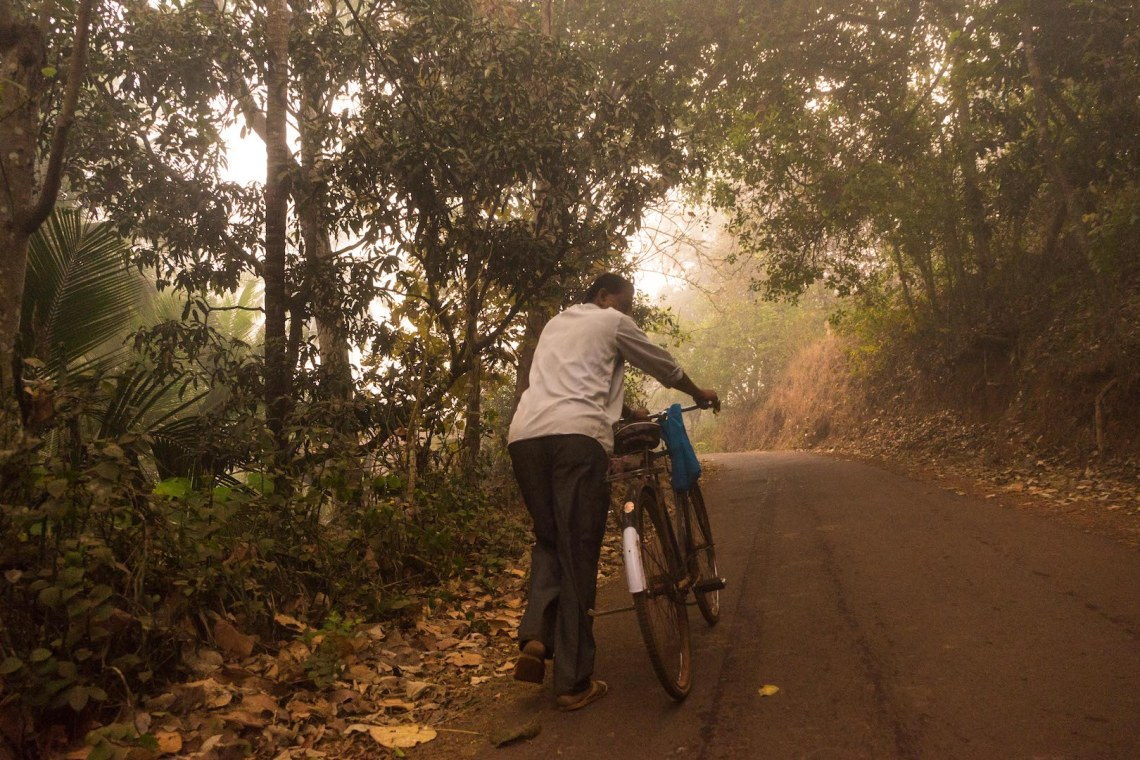 A person pushing around their bicycle in the morning in India