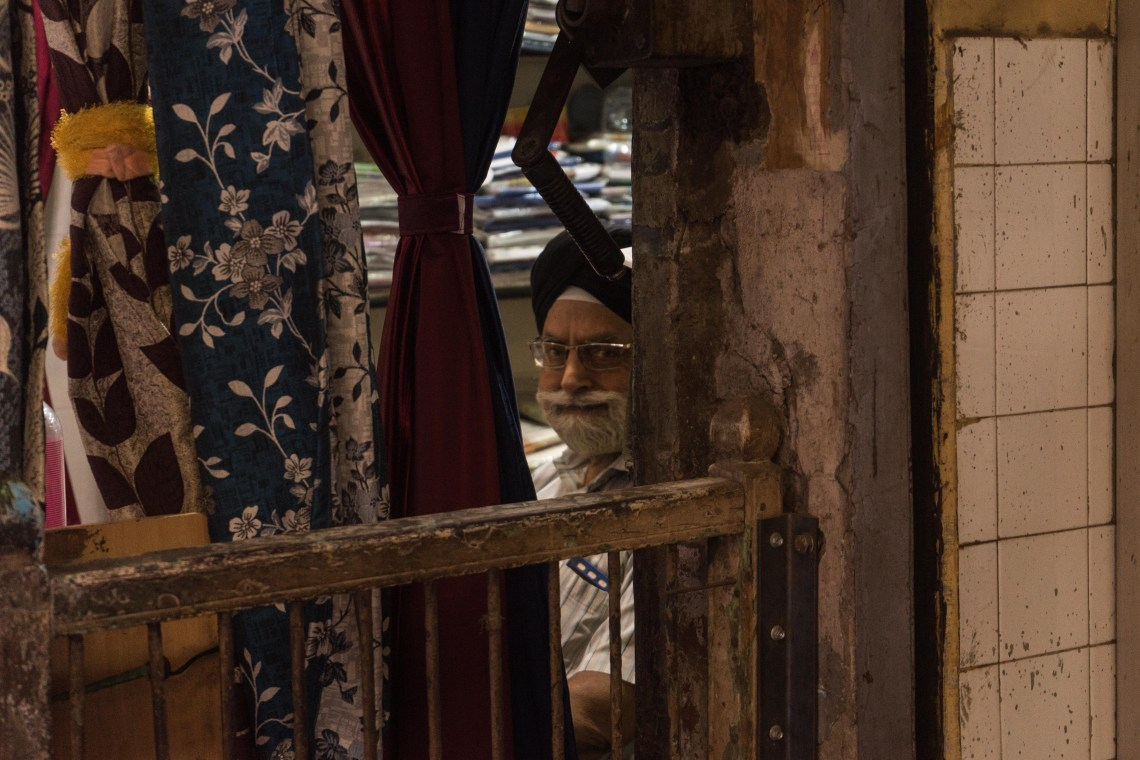 An old man smiling through the curtains of his store directly looking at the photographer in the cloth market in Delhi, India