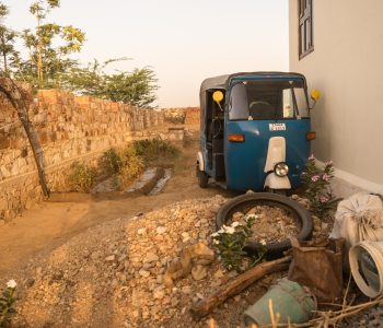 A tuk tuk standing close to a pile of rubble