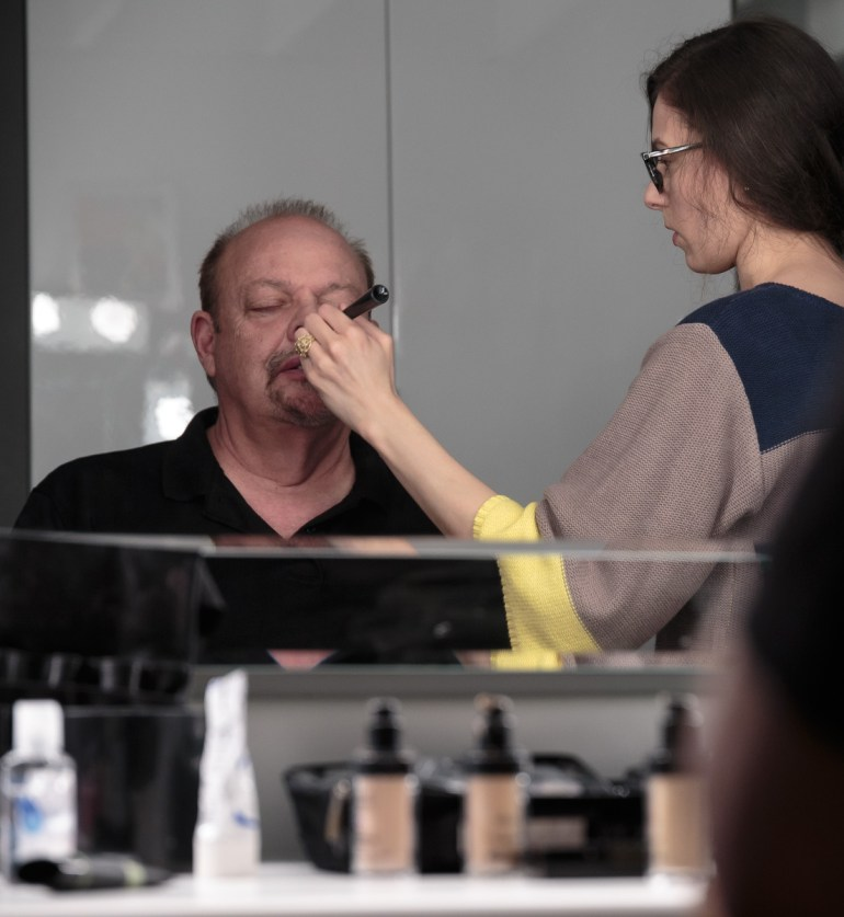 Amy George applies Kevin's makeup.