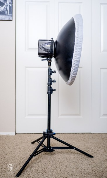 This is the right way to position a light, with one leg of the stand under the heaviest part of the light.