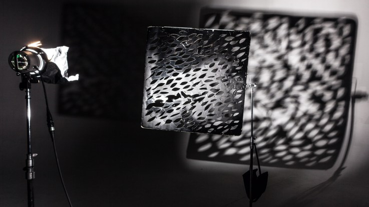 A small light shining through leaf shaped cutouts cast shadows on the background.