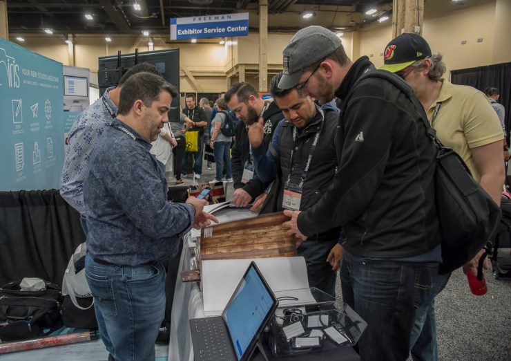 Chales Kaufman of Click Props discusses backgrounds with a customer at WPPI