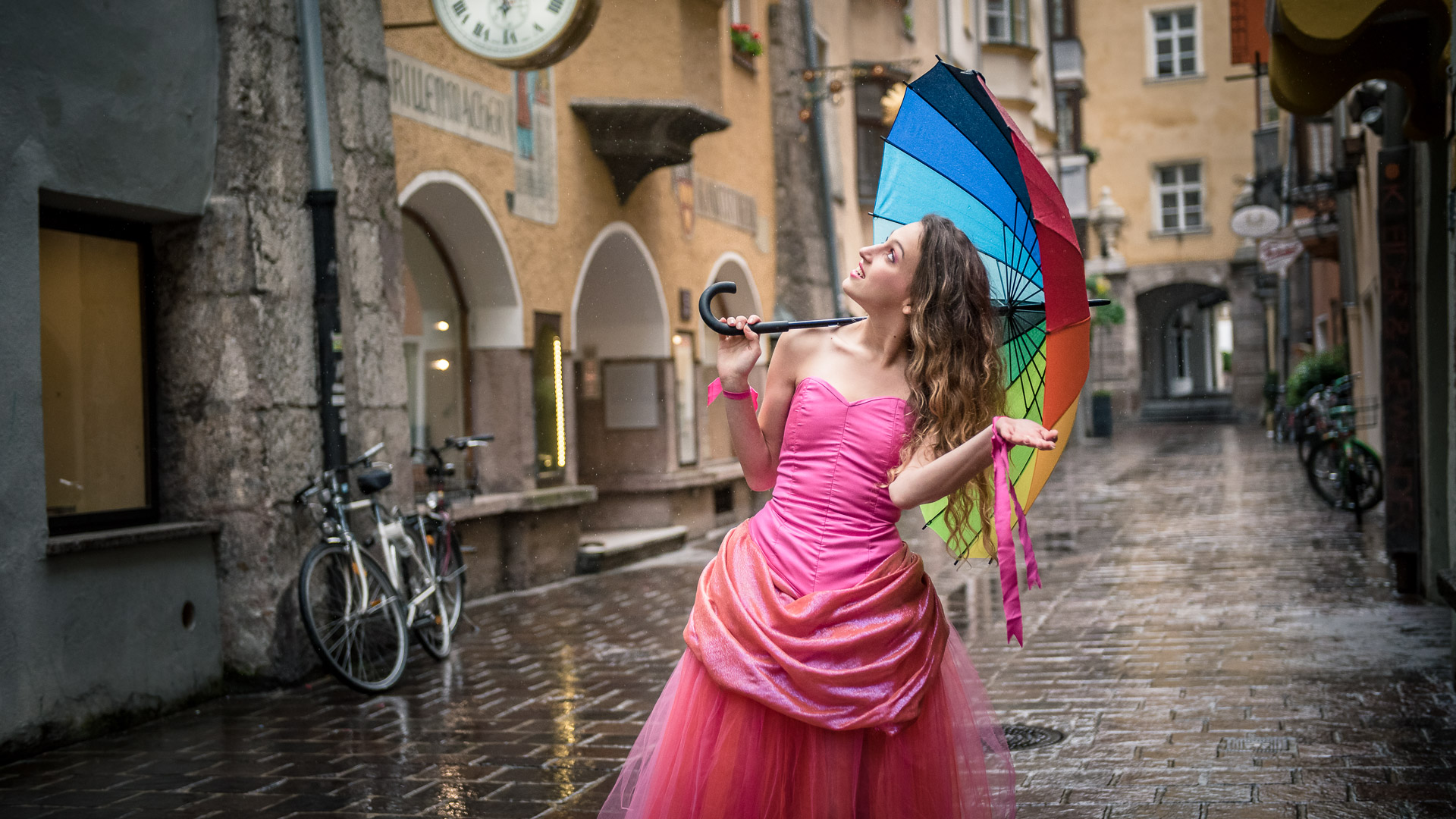 girl, pink dress, rain, umbrella, rainbow umbrella, old city, cobbled street, tulle skirt, corset