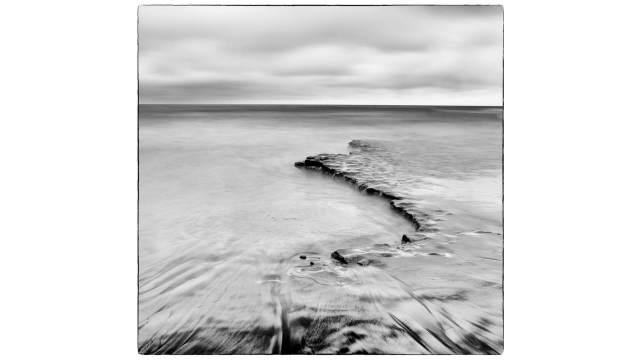 Dreamy monochrome seashore scene with moody sky