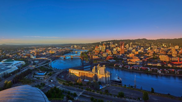 Drone aerial at sunrise with 6 bridges shot from over the top of the Moda Center of downtown Portland on a summer morning