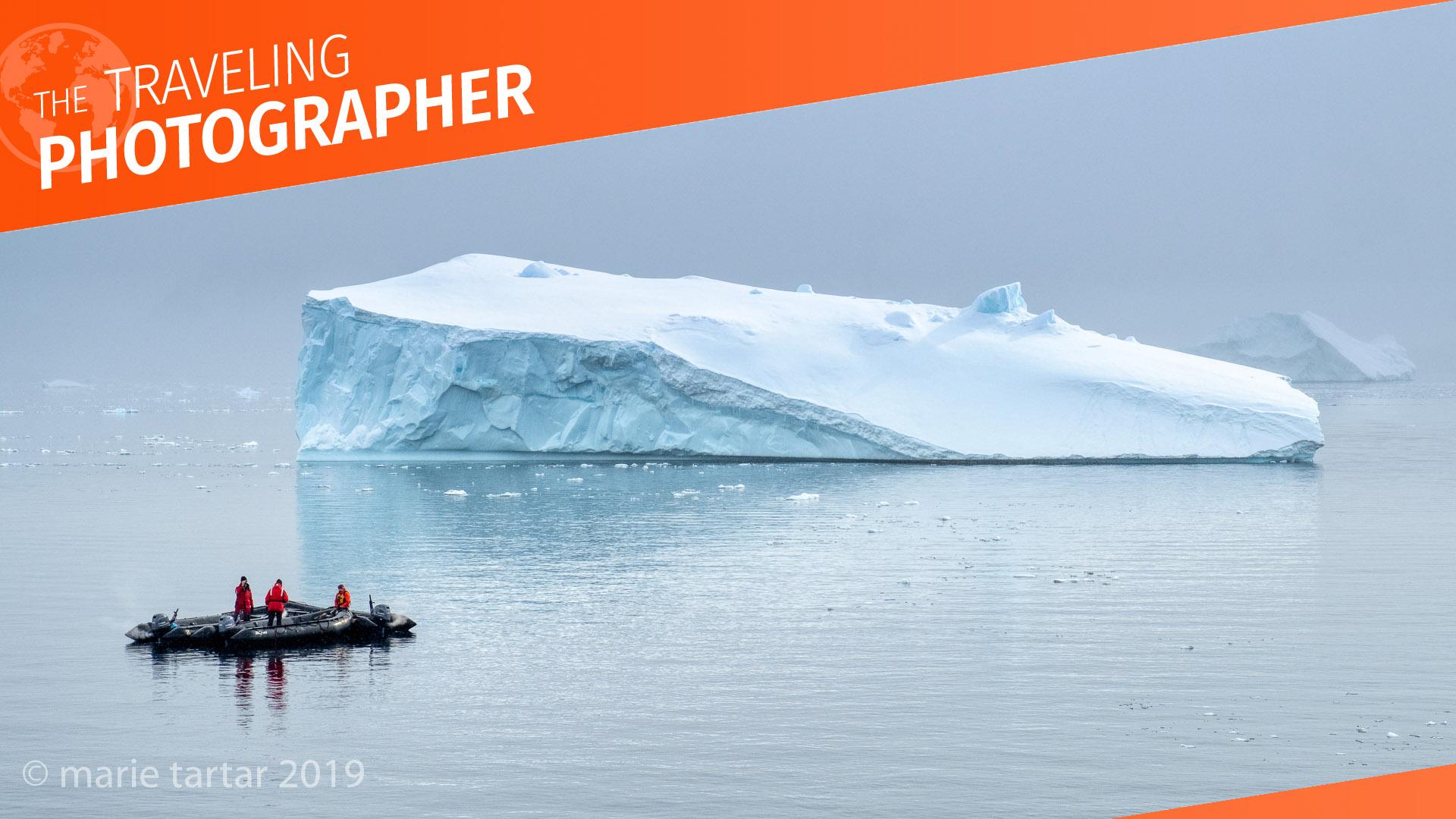 Travelers in a zodiac admire an iceberg in Antarctica