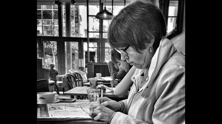 """Untitled"" a woman working a crossword in a coffee shop provides the Photographer of the Day from Photofocus honors to thesrpspaintshop"