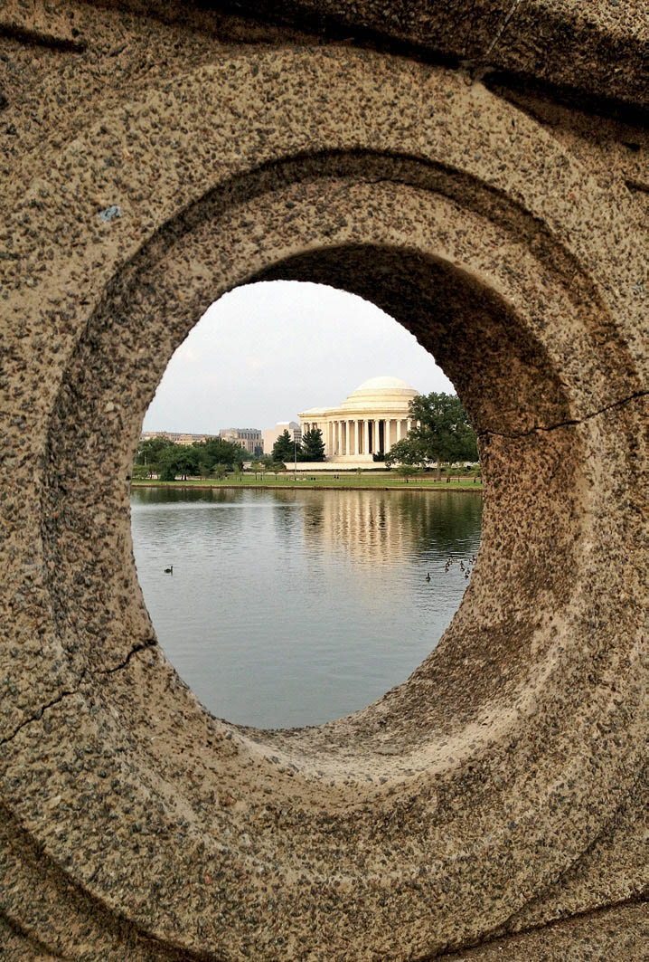 A porthole on a bridge frames the Jefferson Memorial.