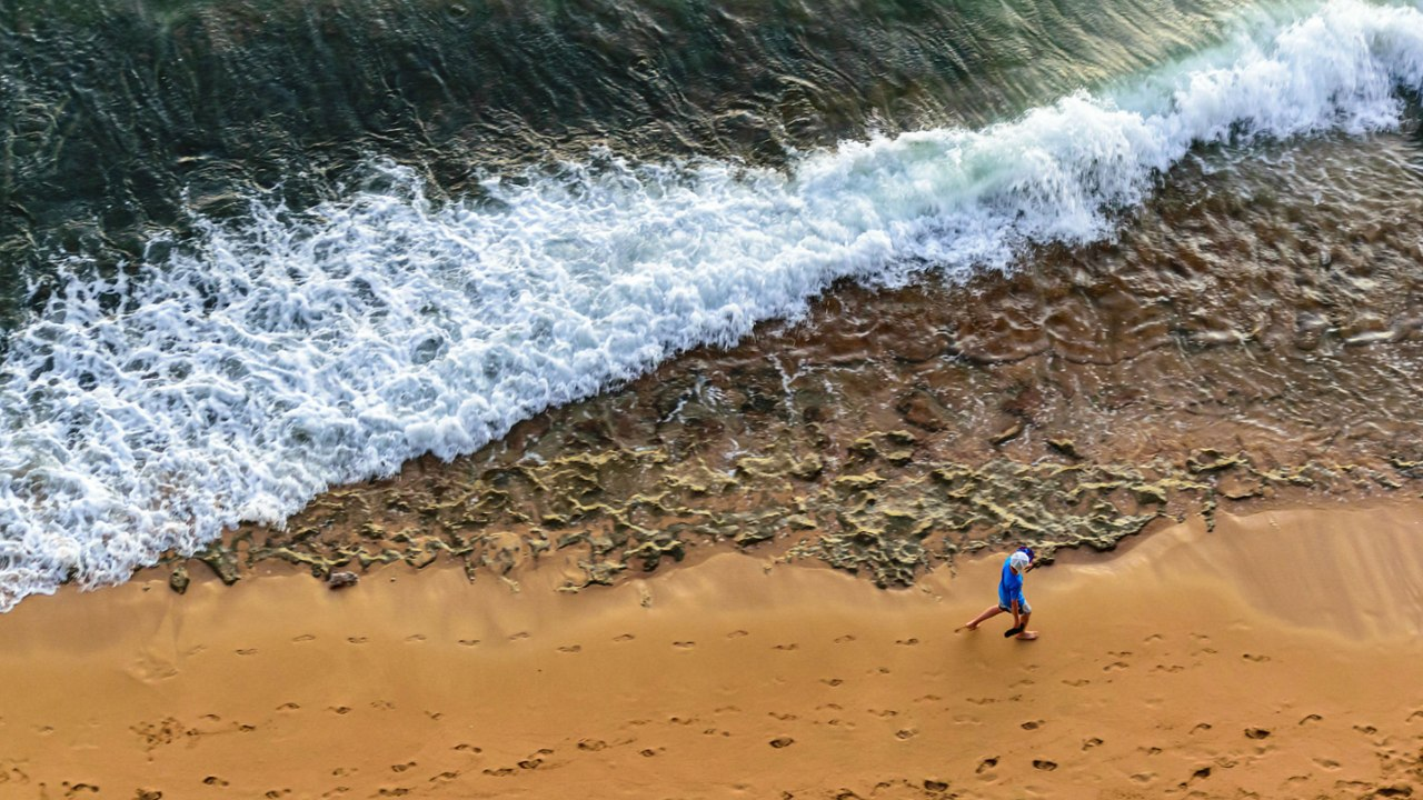 man walking beach from above
