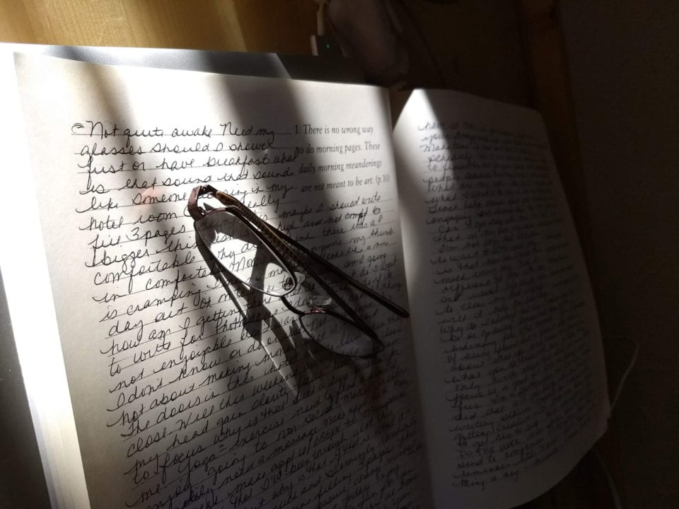 writing on paper with glasses