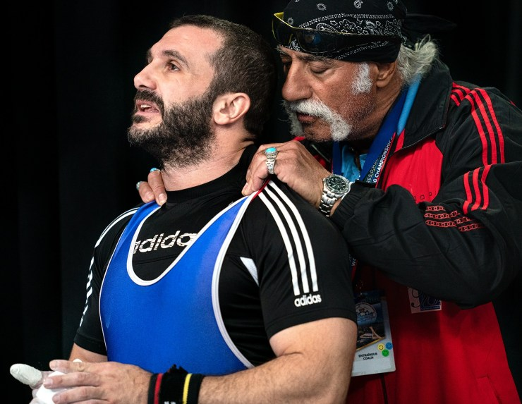 A weightlifting coach helps his athlete focus before his lift