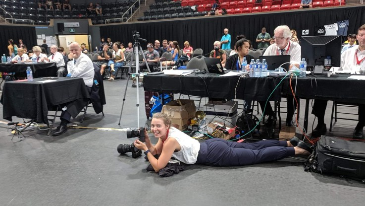 Female photographer installed on the floor with camera gear for her first international sports event coverage