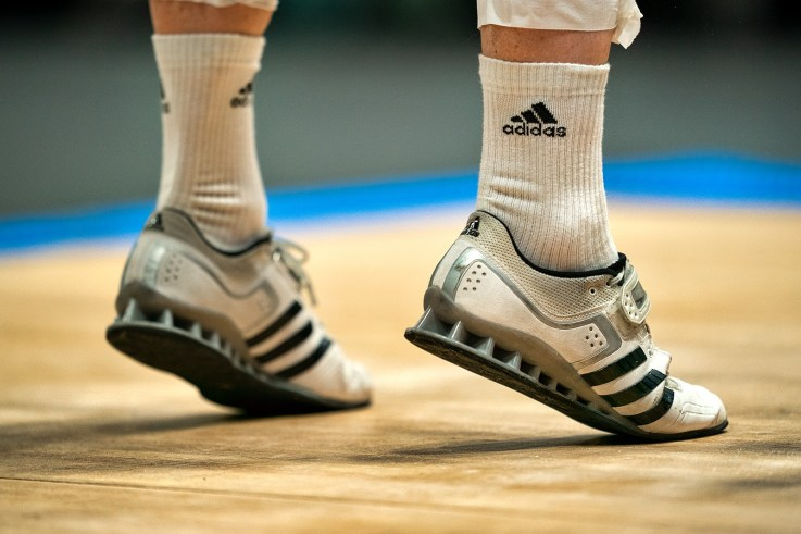Adidas sports shoes international athlete jumping to pull a bar in a wooden platform