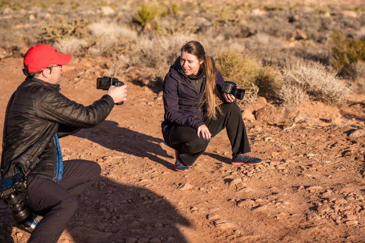 Female and male photographers talking together desert