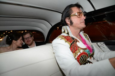 Photographers of Las Vegas - Wedding Photography - wedding bride and groom riding in Pink Cadillac with Elvis impersonator