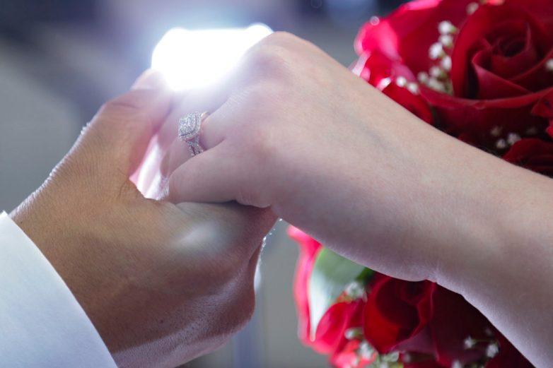 Photographers of Las Vegas - Wedding Photography - wedding rings on hands with flowers light behind