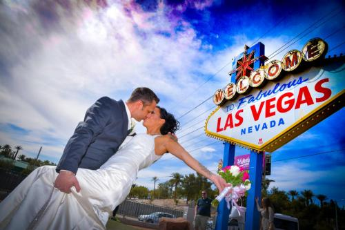 Photographers of Las Vegas - Vegas Strip Tour Photography - Groom dips the bride and they kiss at the iconic Vegas Sign