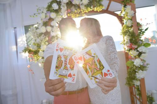 Photographers of Las Vegas - Wedding Photography - wedding couple sun flare as bride and groom kiss with King and queen of hearts
