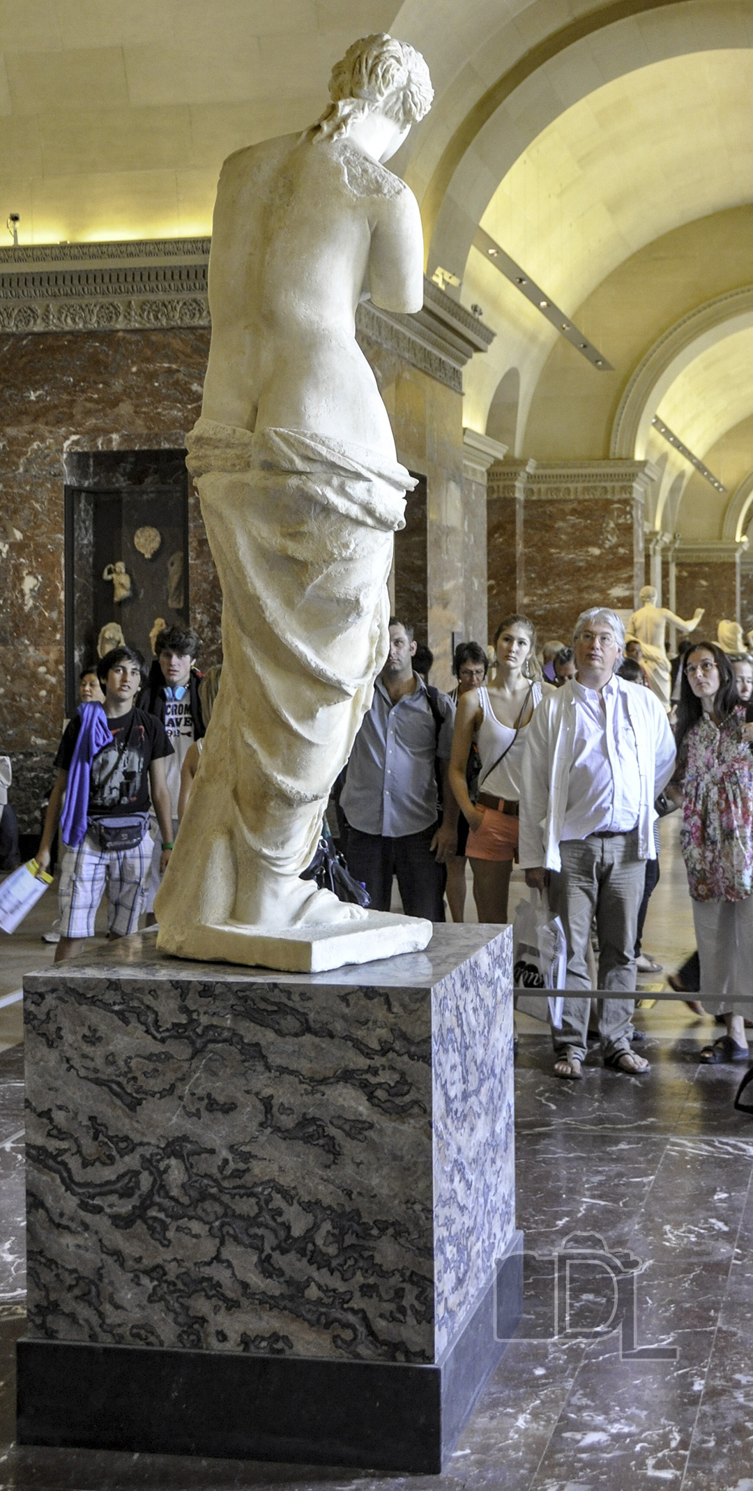 Tourists at The Louvre in Paris engage in a staring contest with Alexandros of Antioch's Venus de Milo statue.