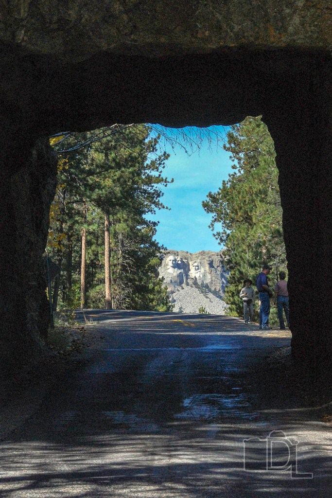The granite heads of Mount Rushmore are framed by a tunnel on Iron Mountain Road.