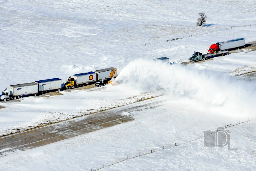 A highway plow helps free a convoy of stuck tractor-trailers along a snow-covered interstate.