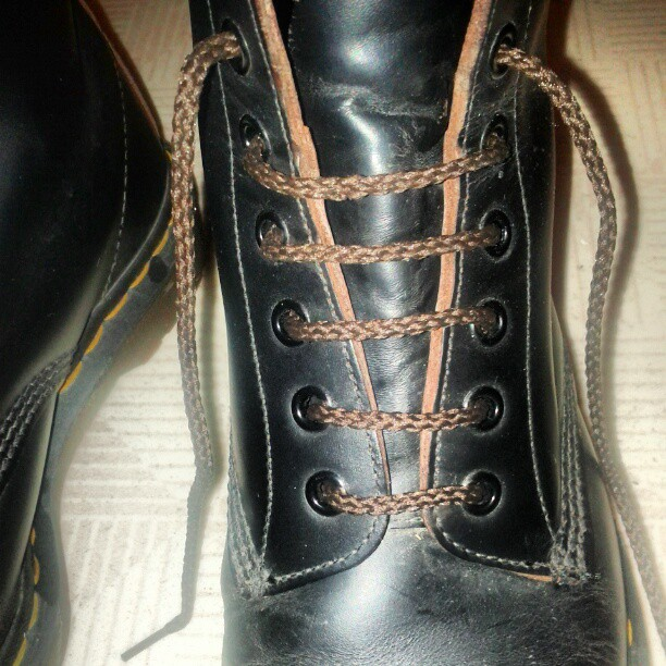 a photo of a blacked boot laced-up with a brown lace