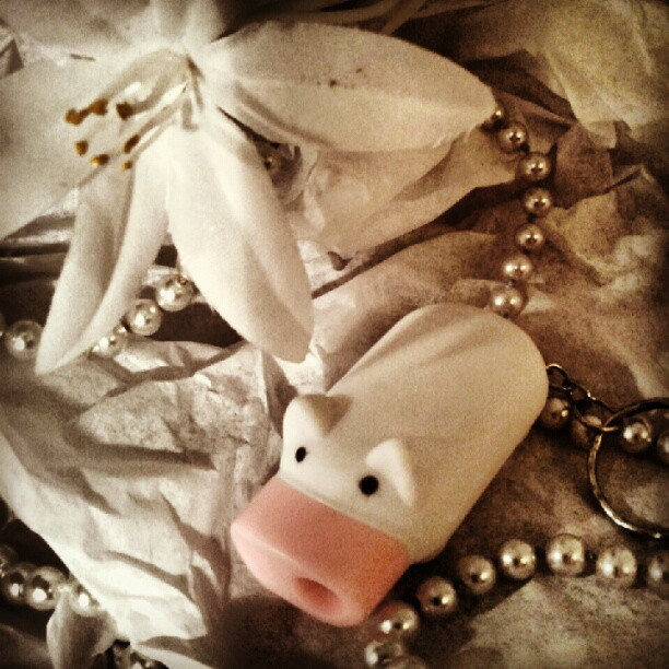 a photo of a silk flower, a toy pig and a pearl necklace