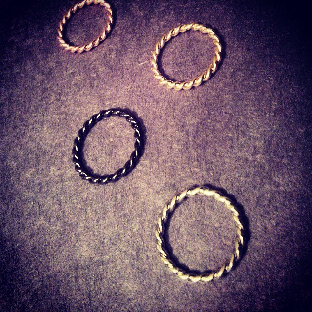 a photo of four twisted metal rings in four different colours