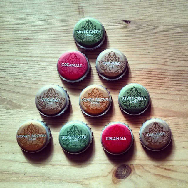 a photo of assorted sleeman beer bottle caps arranged in a triangular patter