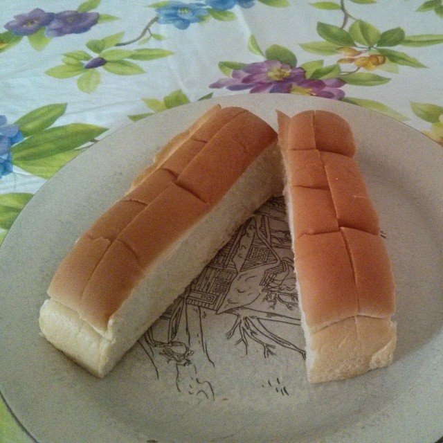 a photo of two topslice hotdog buns on a plate