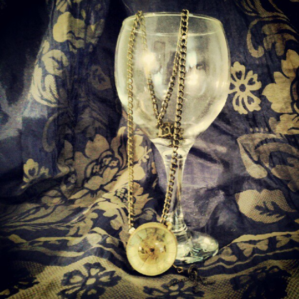 a photo of a watch with its chain draped into a wine glass