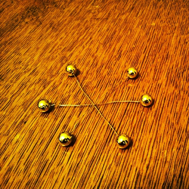 a photo of a three wires with beads on both ends, they are in a star-shaped configuration