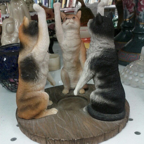 a photo of a weird decoration with three cats doing a strange salute
