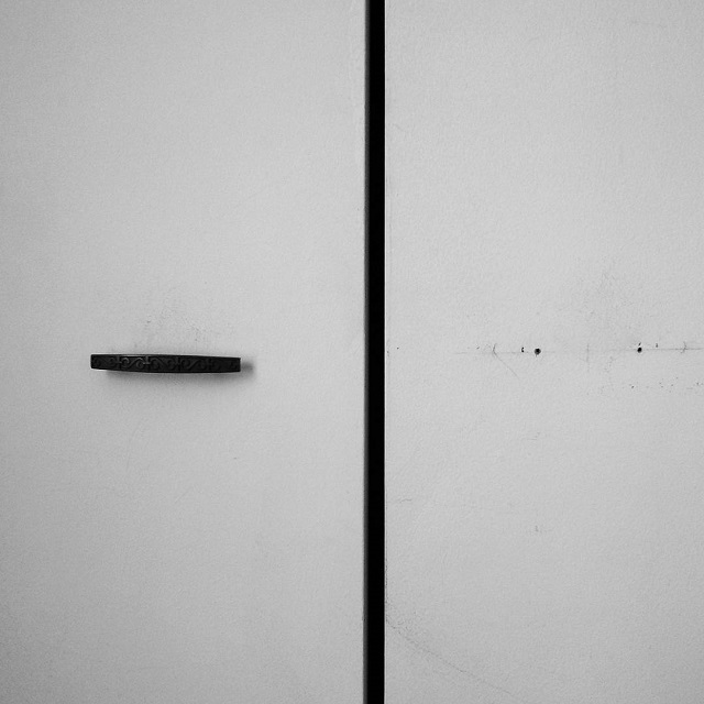 a black and white photo of a closet doors and one is missing its handle